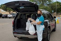 Image of CNS staff loading packaged food into car