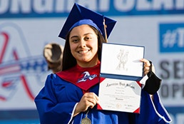 Americas High School student showing her new diploma at the graduation ceremony